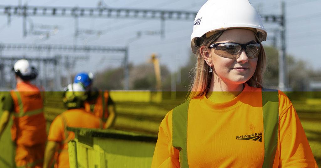 Female rail graduate in orange Network Rail uniform and hard hat gazes across rail tracks.